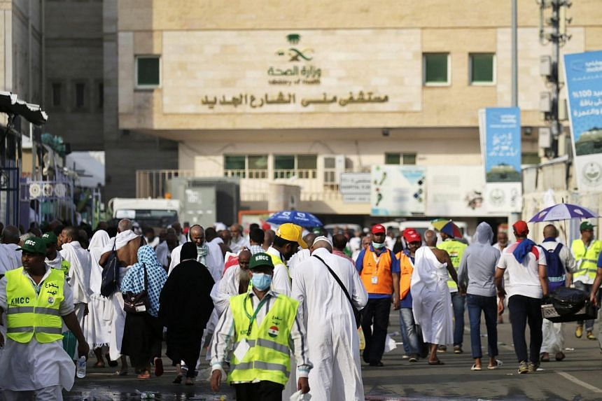 Pilgrims and volunteers walk along a street in front of a hospital near the site of a stampede earlier in the day in the Mina neighborhood of Mecca, Saudi Arabia, on Sept 24, 2015.