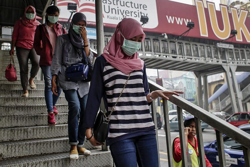 Malaysians wear face masks as a thick haze hovers over Kuala Lumpur, Malaysia, on Sept 26, 2015.