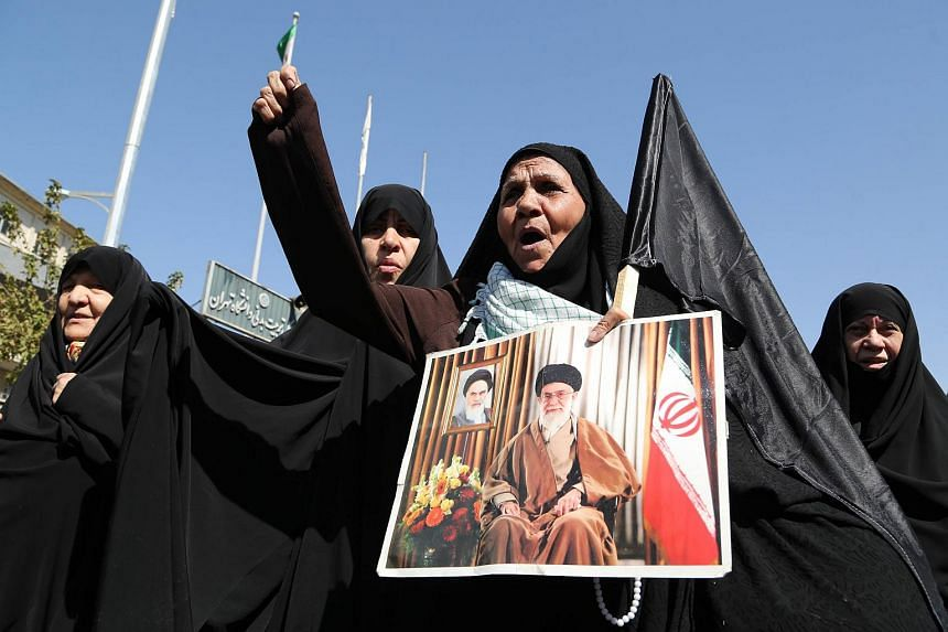 An Iranian protestor holding a picture of Iran's supreme leader Ayatollah Ali Khamenei during a demonstration at Tehran's Enghelab square, against Saudi Arabia, after 131 Iranian pilgrims were killed in a stampede at the annual haj.