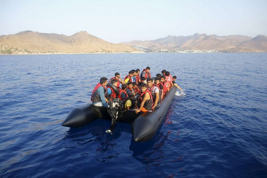 Migrants on a dinghy with a broken motor drift away as they try to reach the Greek Island of Kos after leaving Bodrum, Turkey, in the hopes of crossing the Mediterrean Sea, on Sept 20, 2015.