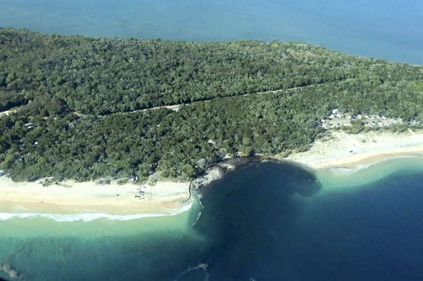 A handout image shows a 150m-long and 50m-wide sinkhole which opened up at Inskip Point, Australia, on Sept 27, 2015, and swallowed a car, a caravan, a camping trailer and tents.