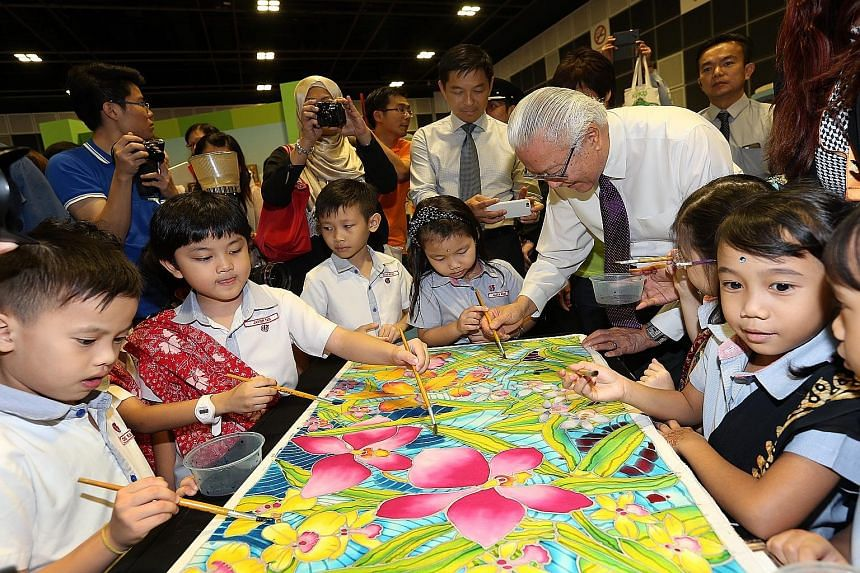 President Tony Tan Keng Yam adding his touch to artwork by children from PCF Sparkletots Preschool @ Eunos Block 650. With the President is Social and Family Development Minister Tan Chuan-Jin.