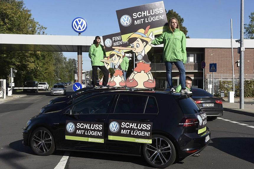 "Greenpeace activists standing on the roof of a Volkswagen car holding banners that say ""No more lies"", outside the company's headquarters in Wolfsburg, Germany. The carmaker used a ""defeat device"" that put a lid on vehicle emissions but only during t"