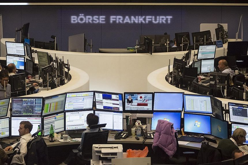 Financial traders monitoring data on computer screens at the Frankfurt Stock Exchange in Frankfurt, Germany, on Friday. Since Volkwagen's deception came to light, its stocks have plunged.