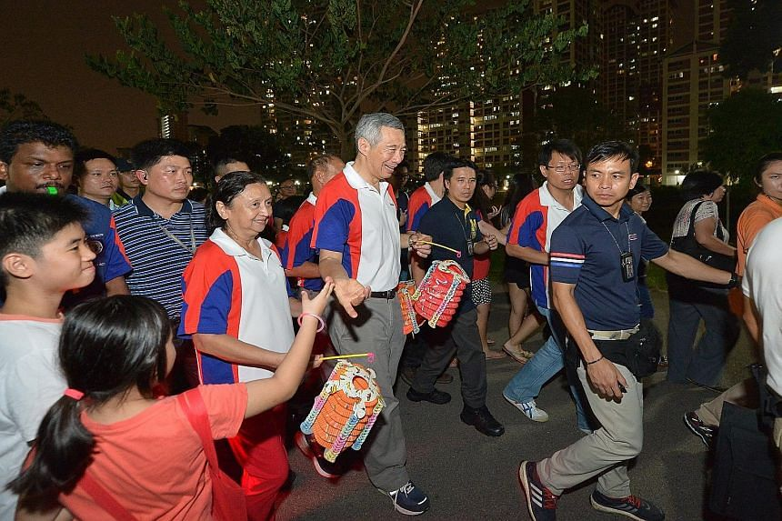 """Prime Minister Lee Hsien Loong joining residents in a lantern procession at Bishan-Ang Mo Kio Park last night. Mr Lee said he hoped """"we will have a good year ahead and next year will be better""""."""