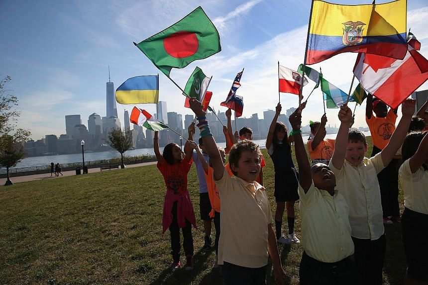 Fourth and fifth graders cheering as immigrants take part in a US naturalisation ceremony on Sept 17 in Jersey City. Immigrant families in the United States trail those in Britain, Canada, France, Germany and the Netherlands when one compares income
