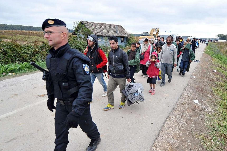 Migrants and refugees walk across the Serbian-Croatian border on Sept 26, 2015.