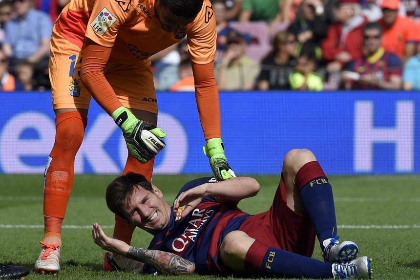 Barcelona's Argentinian forward Lionel Messi (bottom) complains after being injured, next to Las Palmas' goalkeeper Javi Varas.