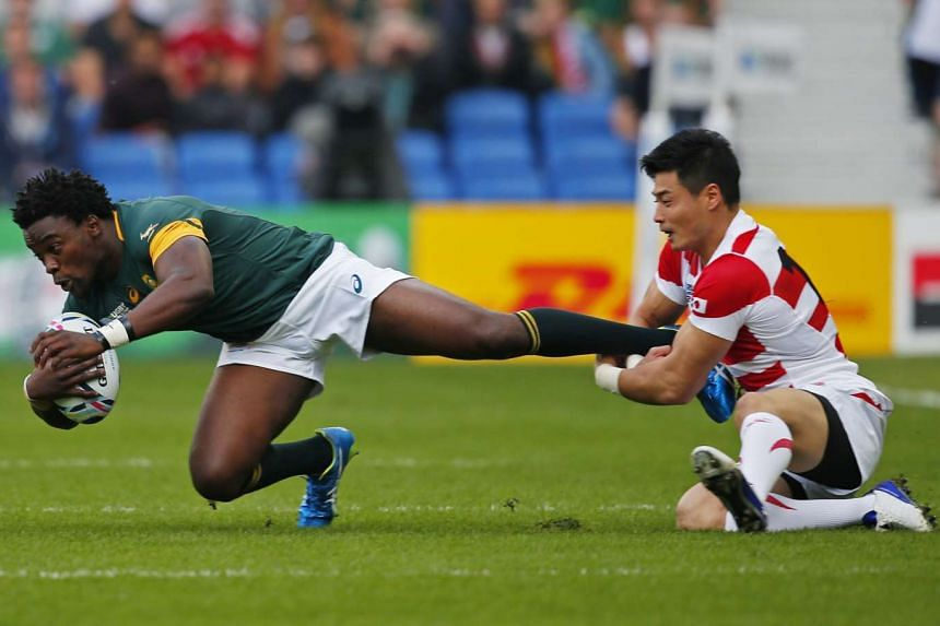 Japan's Akihito Yamada (right) in action with South Africa's Lwazi Mvovo during the two countrys' Rugby World Cup match last week.