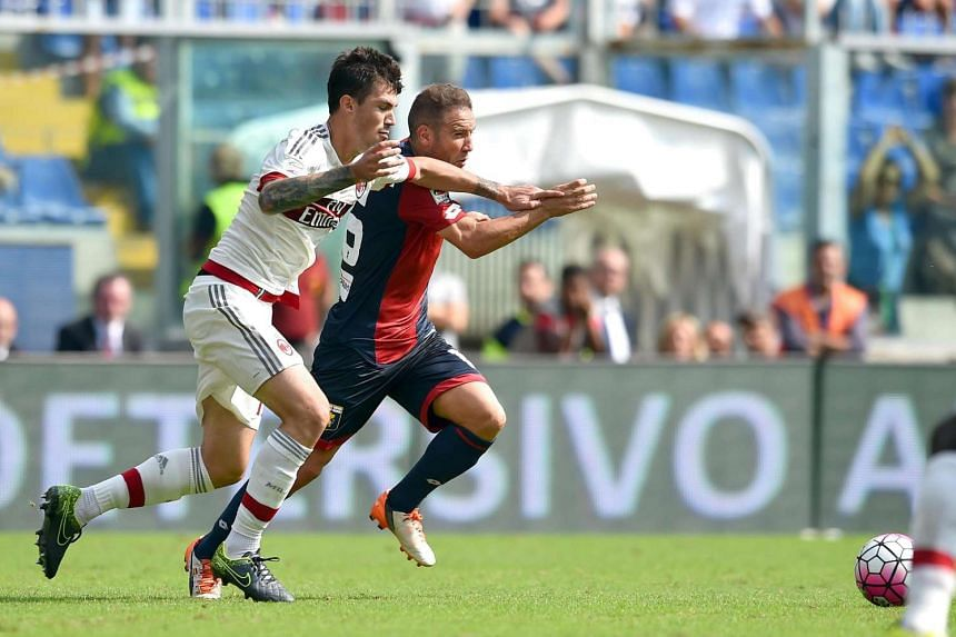 Milan's defender Alessio Romagnoli (left) hits Genoa's Spanish forward Diego Angel Capel with his elbow during the Italian Serie A soccer match on Sept 27, 2015.