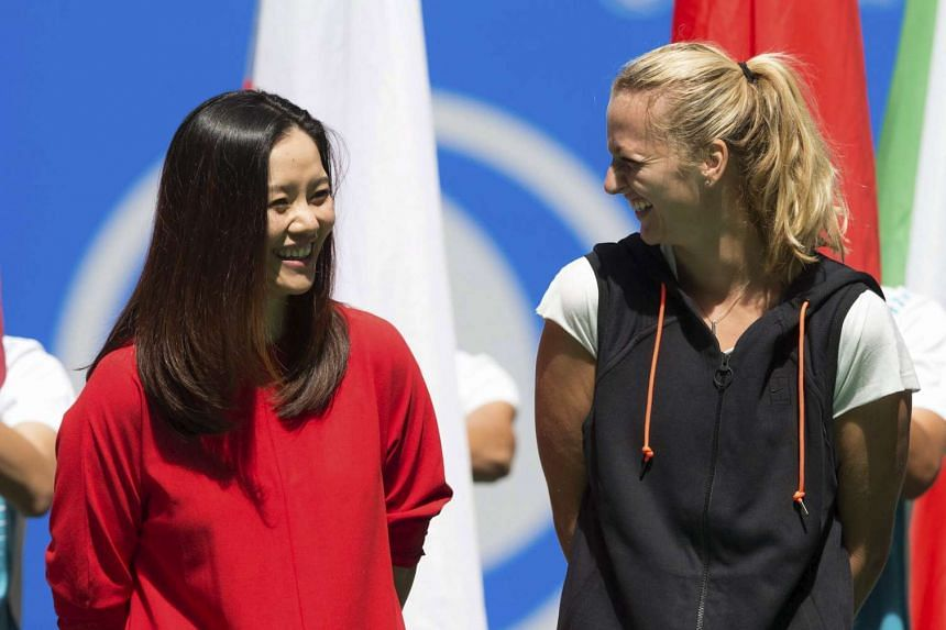 Former Chinese tennis player Li Na (left) smiles as she talks to defending champion Petra Kvitova of the Czech Republic during the opening ceremony at the Wuhan Open tennis tournament on Sept 27, 2015.