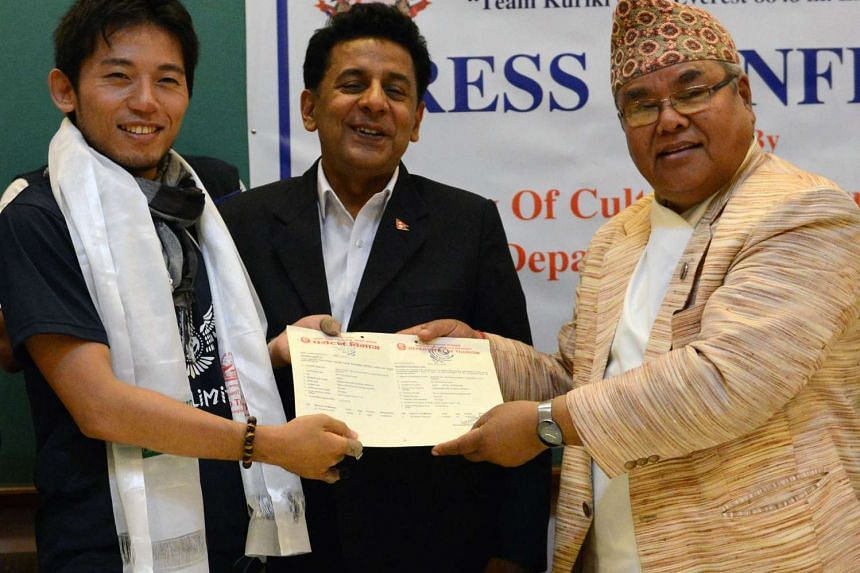 Kuriki (left) accepting his permit to climb Everest from Nepal tourism minister Kripasur Sherpa (right).