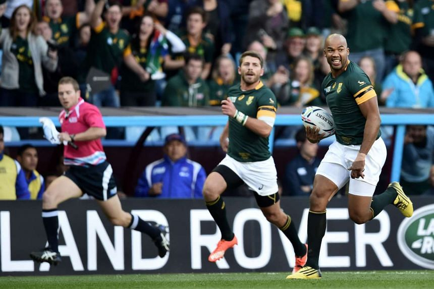 South Africa's wing JP Pietersen (right) runs to score the team's first try.