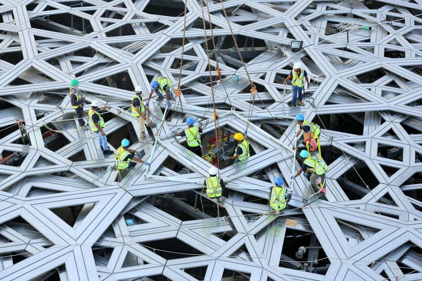 Workers place the final piece of the outer cladding of the dome structure of the future Louvre museum still under contruction on Saadiyat island, near Abu Dhabi.