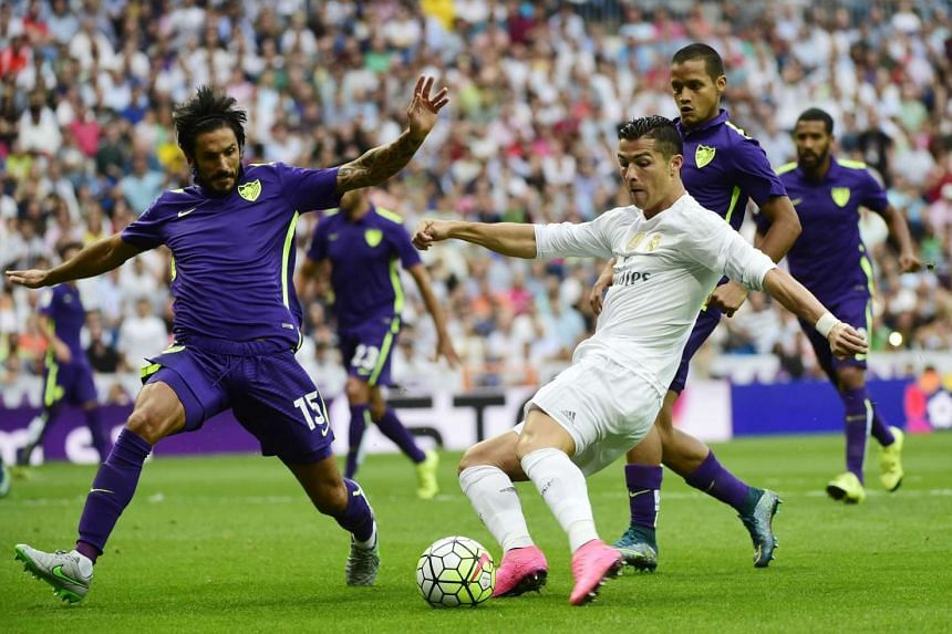 Real Madrid's Portuguese forward Cristiano Ronaldo (right) vies with Malaga's Argentinian defender Marcos Angeleri.