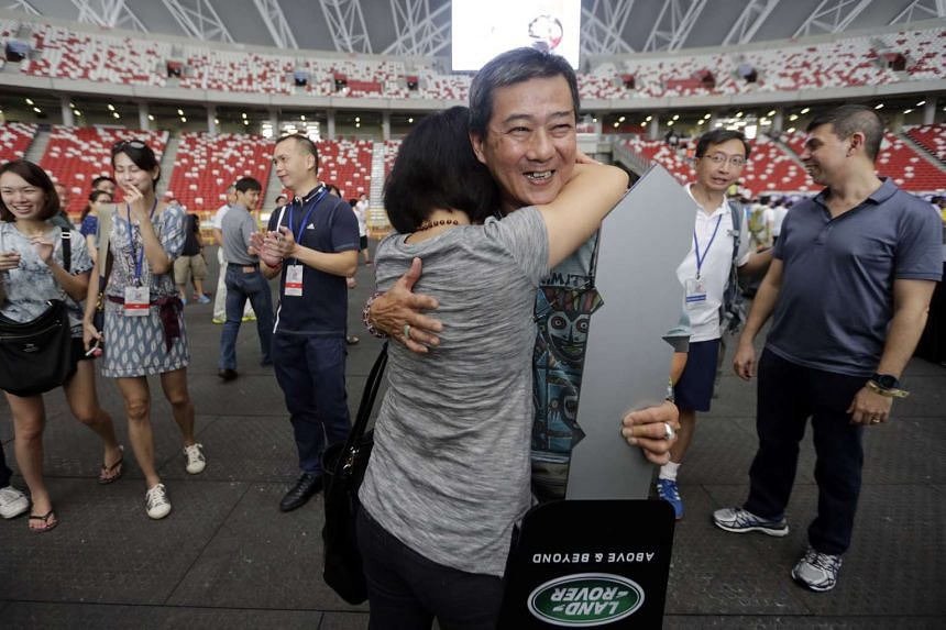 Mike Lim receiving a hug from his wife after winning the Land Rover.
