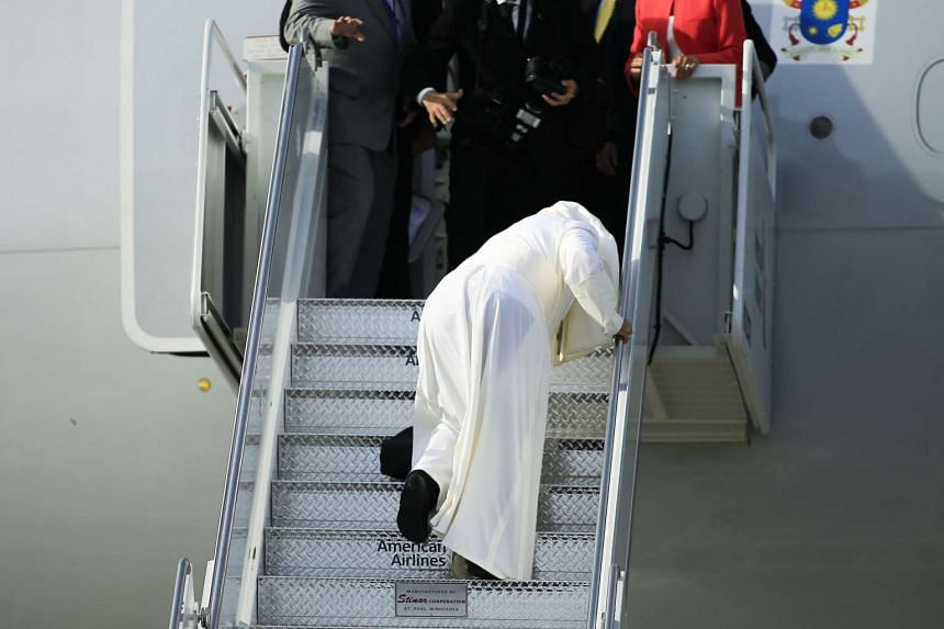 Pope Francis stumbles while boarding his plane from New York to Philadelphia.
