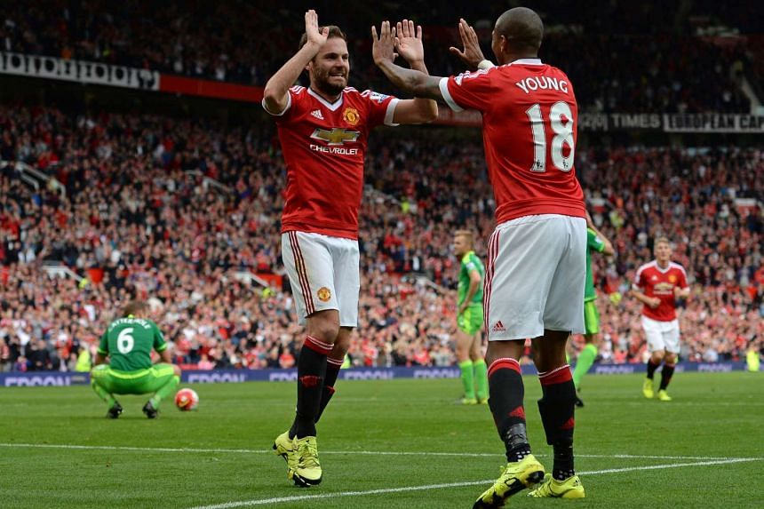 Manchester United midfielder Juan Mata (second left) celebrates with team mate AshleyYoung after scoring their third goal.