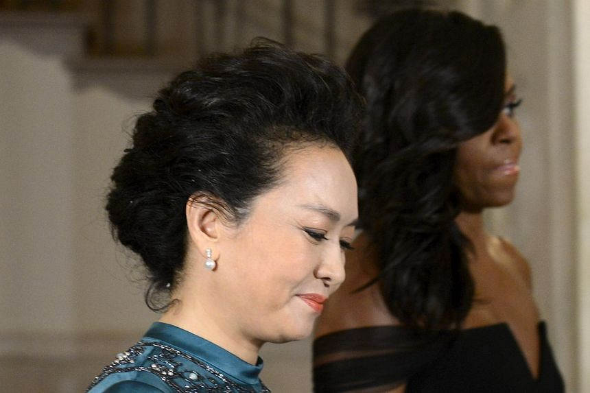 First lady Michelle Obama (right) escorts Madame Peng Liyuan, wife of China's President Xi Jinping, to the State Dinner at the White House in Washington on Sept 25, 2015.