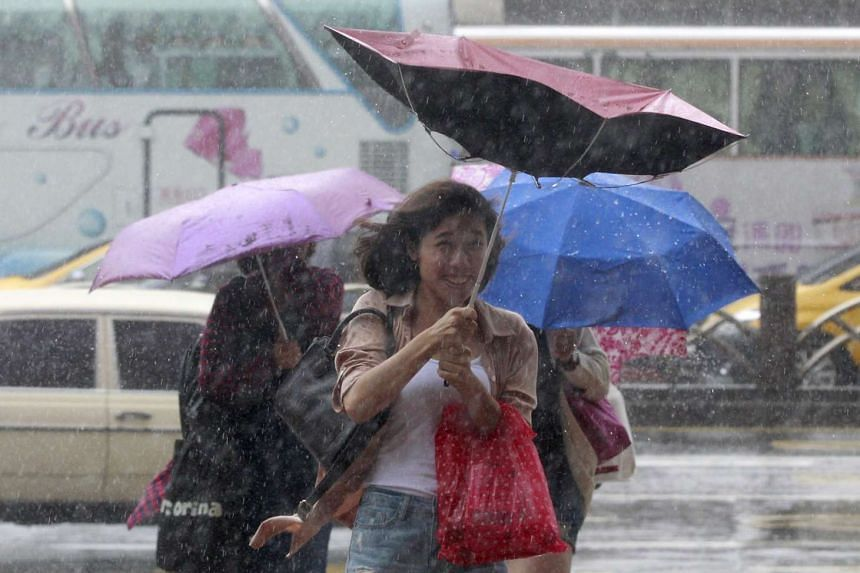 People hold their umbrellas while walking against strong winds caused by Typhoon Dujuan in Taipei, Taiwan, September 28, 2015.