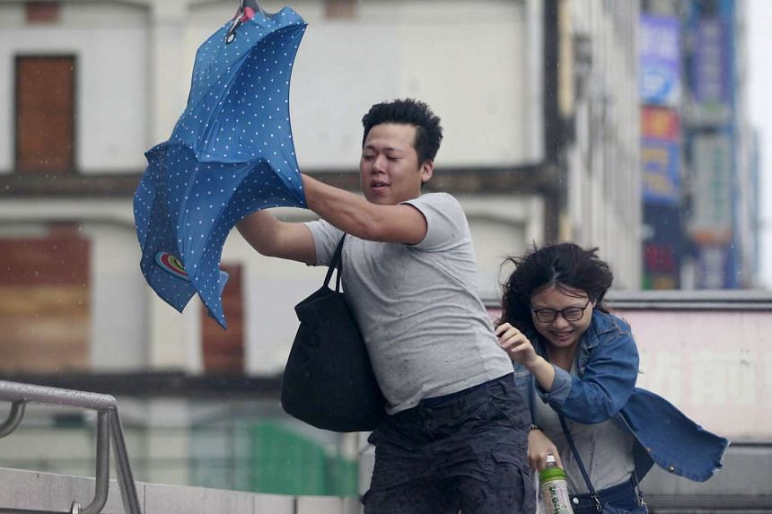 People hold onto their umbrella while walking against strong winds caused by Typhoon Dujuan in Taipei, Taiwan, September 28, 2015.