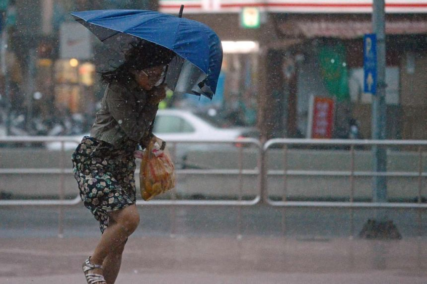 A woman uses an umbrella against strong wind and rain brought by typhoon Dujuan at Tamshui district, New Taipei City on September 28, 2015.