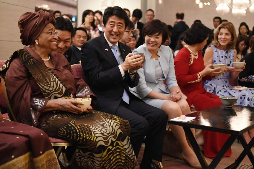 Liberia's President Ellen Johnson Sirleaf (left) smiling with Japan's Prime Minister Shinzo Abe and his wife Akie (centre) as they attend a tea ceremony presentation with Vietnam's Deputy Chairwoman of the National Assembly Nguyen Thi Kim Ngan (2nd f