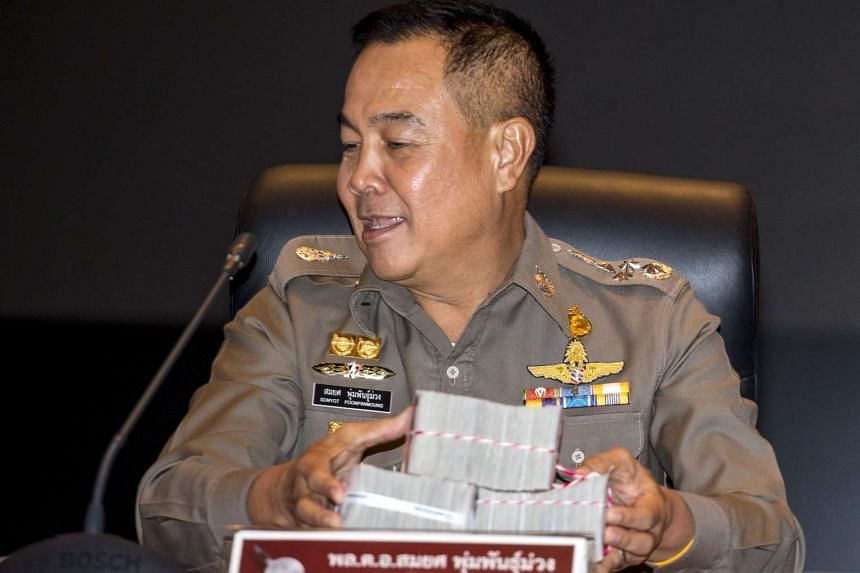 Thai national police chief Somyot Pumpanmuang holding up a reward before a news conference about the Bangkok blast which killed 20 people, including foreigners, at the Royal Thai Police headquarters in central Bangkok, Thailand, on Sept 28, 2015. The