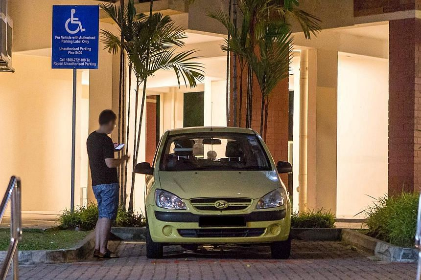 A man leaving his car in a reserved space at a block in Tampines Street 45. A committee has been formed to review the parking system for the disabled.