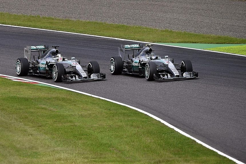 Hamilton (left) overtaking pole-sitter Rosberg at the start of the Japanese Grand Prix to seize the initiative yesterday. He then comfortably held on to the lead to bag his eighth win of the season.