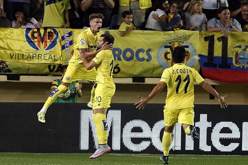 Villarreal forward Leo Baptistao jumping with joy while celebrating his winner with his team-mates. The result means they lead Barcelona by a point and Real Madrid by two.