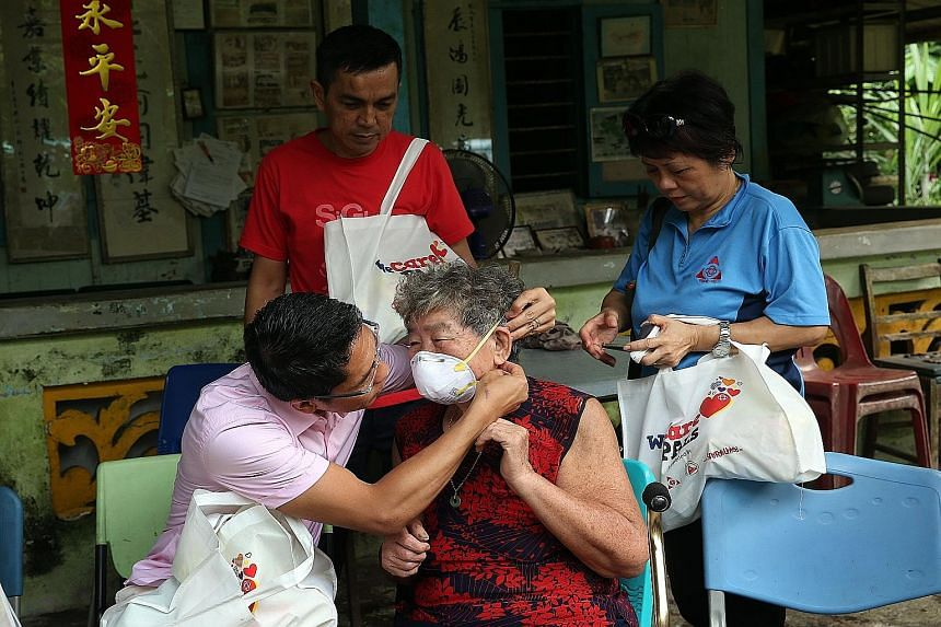 Dr Maliki Osman showing Madam Chen Xiu Zheng, 78, how to wear an N95 mask. Together with volunteers, he gave out WeCare Packs containing masks, eyedrops and other items to residents of Pulau Ubin yesterday. Buildings in the distance shrouded in haze