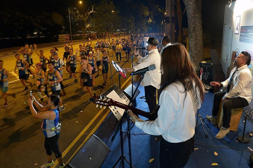 Participants in the 18.45km race being entertained by Shuk And Fren, who belted out 1960s hits from bands like The Beatles. The route took participants past iconic landmarks such as Marina Bay Sands and the Merlion.