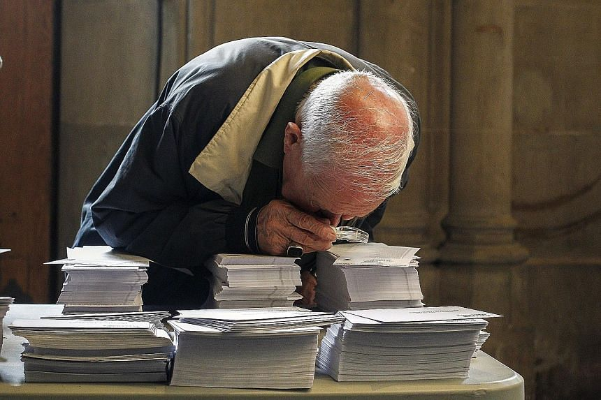 An old man peering at ballot papers in a polling station in Barcelona, Spain, yesterday.