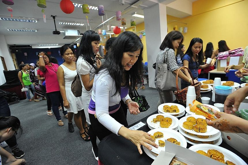 Maid Rita Sahara, 37, sampling some halal mooncake at a Mid-Autumn Festival bazaar at the Fast Clubhouse yesterday. The Foreign Domestic Worker Association for Social Support and Training (Fast) organised a series of activities for 250 maids.