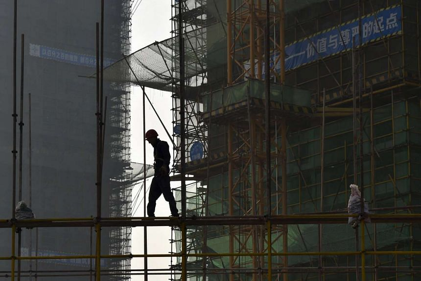 A worker walks on scaffolding at a residential construction site in Hefei, Anhui province, China. Industrial profits tumbled 8.8 per cent in August from a year earlier, sharply down from 2.9 per cent decline posted in July, the National Bureau of Sta