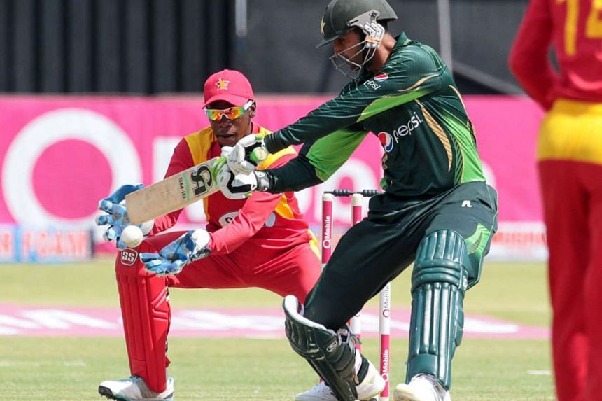 Pakistan's batsman Shoaib Malik (center) in action as Zimbabwe's wicket keeper Richmond Mutumbami looks on (left) during the first of two T20 cricket matches between Pakistan and hosts Zimbabwe at the Harare Sports Club on Sept 27, 2015.