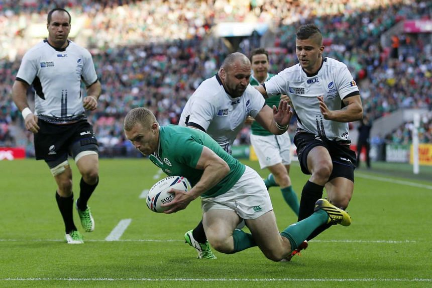 Ireland's Keith Earls scores their third try against Romania during a Rugby World Cup match at Wembley Stadium.
