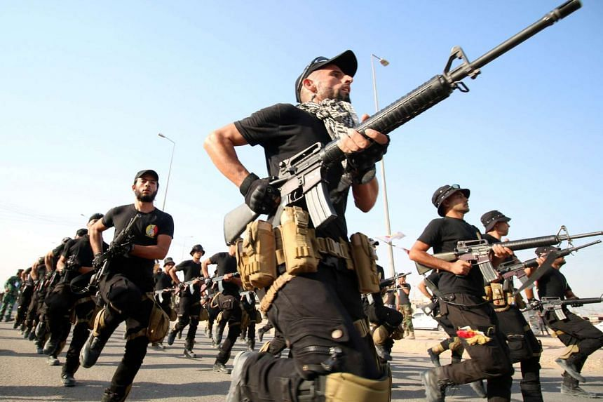 Fighters from the Abbas battalion of the Shiite Popular Mobilisation units march during a military parade in the southern Iraqi city of Basra on Saturday, displaying their skills ahead of taking part in combat against ISIS in Fallujah, east of the ca