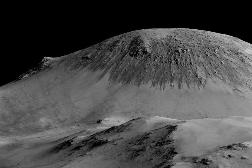 Dark, narrow, 100 metre-long streaks called recurring slope lineae flowing downhill on Mars seen in this handout image made available by Nasa on Sunday are inferred to have been formed by contemporary flowing water.