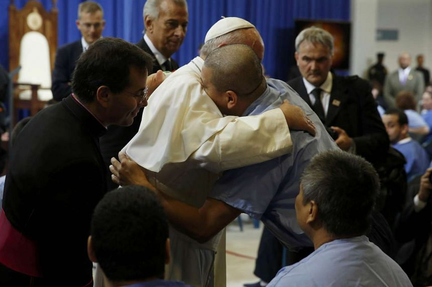 Pope Francis embraces an inmate as he meets with prisoners at Curran-Fromhold Correctional Facility in Philadelphia