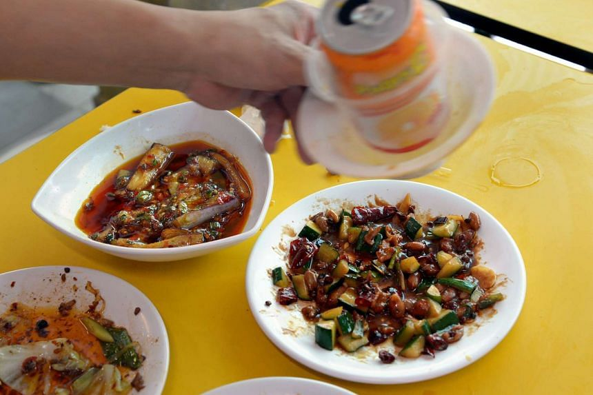 Leftover food at People's Park Hawker Centre in March last year. A record 796,000 tonnes of food were tossed out last year, a 13.2 per cent from the 703,200 tonnes of food waste generated in 2012.