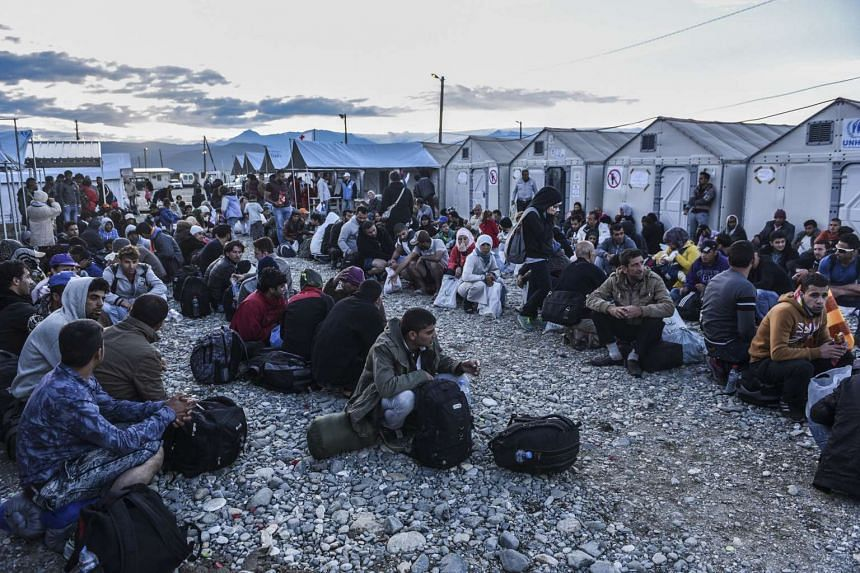 Migrants and refugees wait to board a train near Gevgelija in southern Macedonia after crossing the Greek-Macedonian border.  Many of them from Syria, Afghanistan, Iraq and Somalia.
