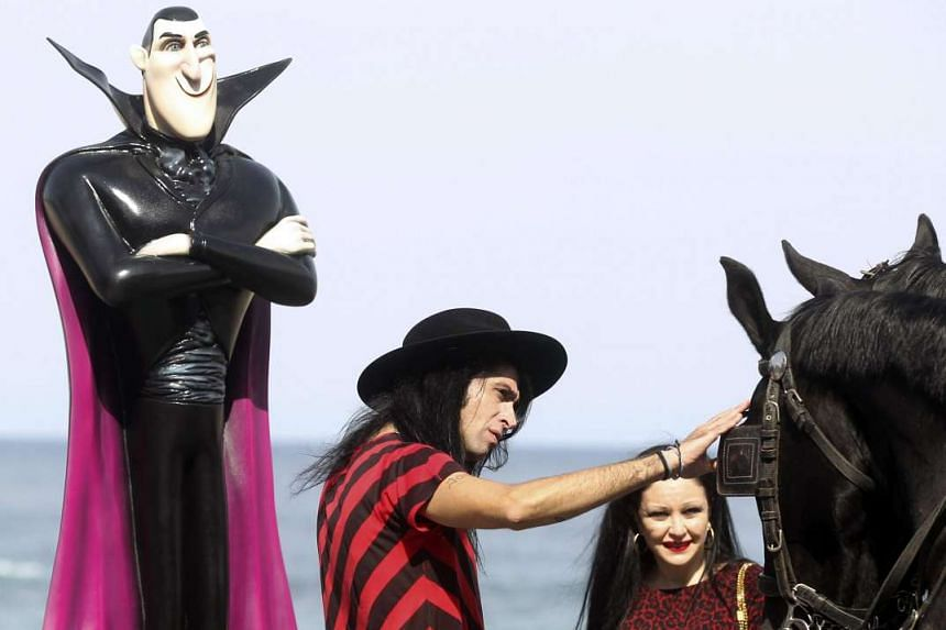 A statue of Count Dracula is seen in the background as Spanish voice actors Mario Vaquerizo (left) and Alaska stroke a horse during a photocall for Hotel Transylvania 2. US actor Adam Sandler voices Count Dracula.