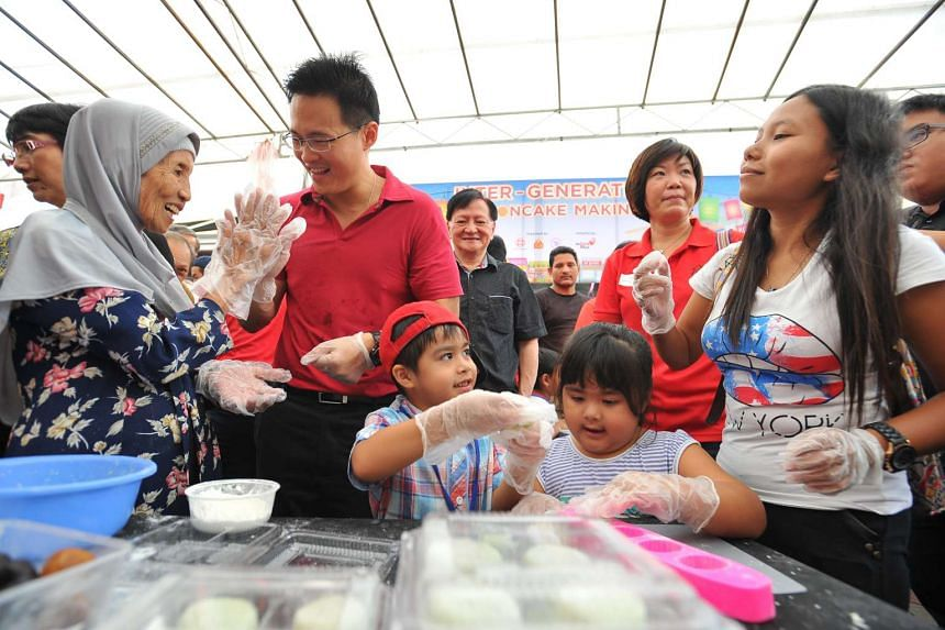 "Tampines GRC MP Desmond Choo giving a high five to Madam Hermin, 80, at the ""Inter-Generation Mooncake Making"" booth at a Mid-Autumn Festival fair in Tampines yesterday."