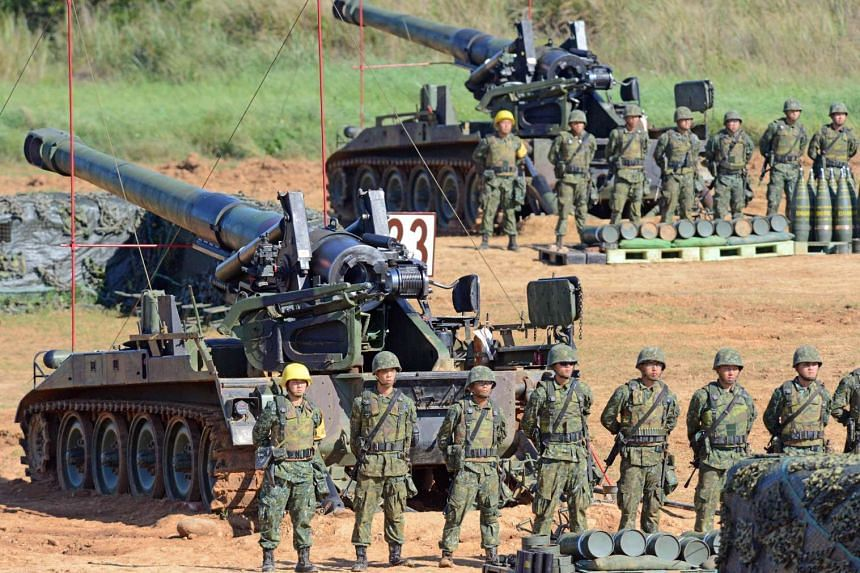 Taiwan military soldiers stand guard next to a 155-millimeter howitzer during the Han Kuang 31 live fire drill in Hsinchu, northern Taiwan, on Sept 10, 2015.