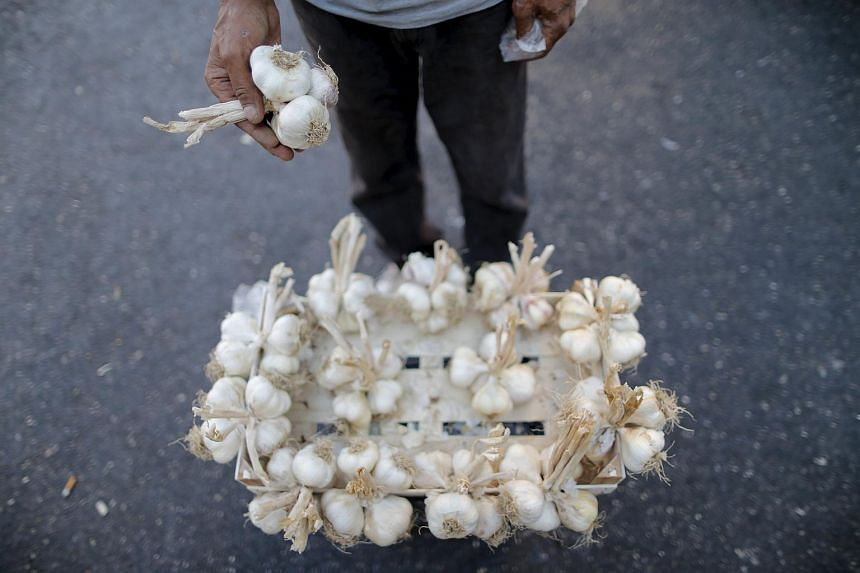 A street vendor sells bulbs of garlic.