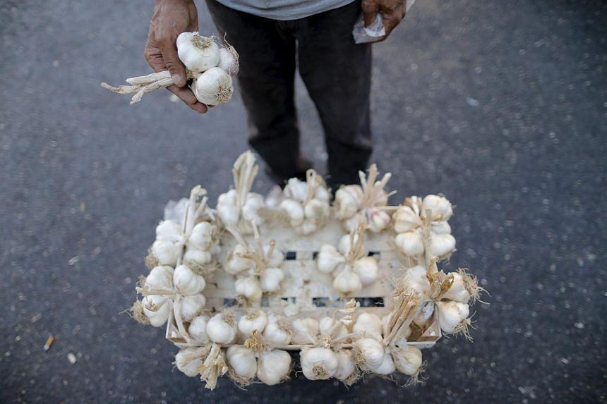 A street vendor sells bulbs of garlic.