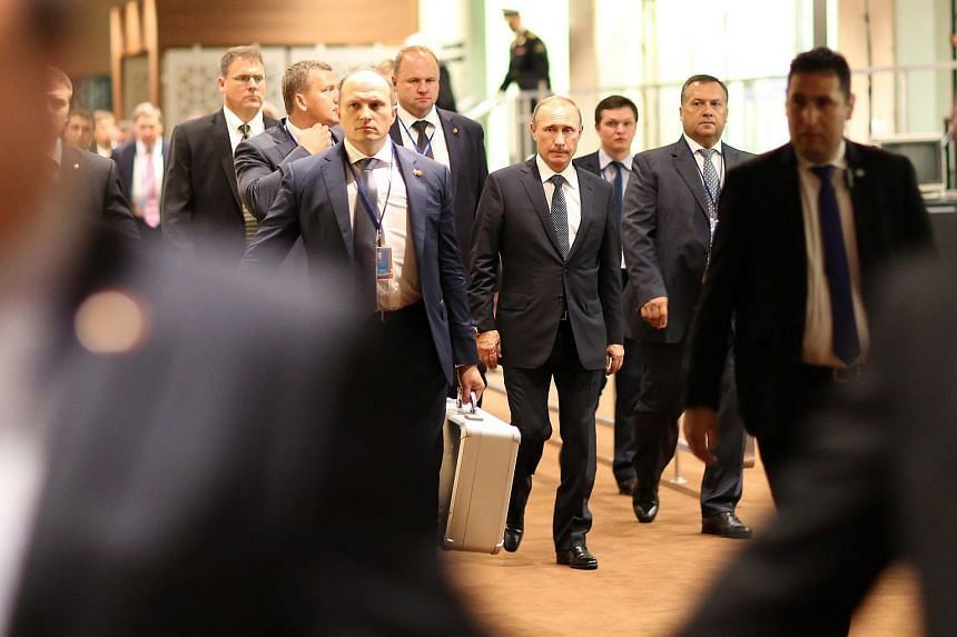 Russian President Vladimir Putin (centre) walks with his security team between meetings during the 70th session of the United Nations General Assembly at United Nations headquarters in New York, New York, USA, Sept 28, 2015.