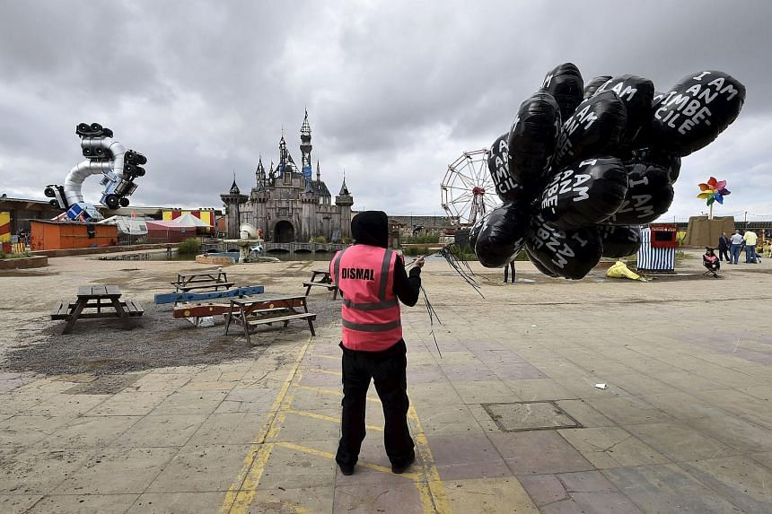A performer holding a bunch of balloons at Dismaland on Aug 20, 2015.